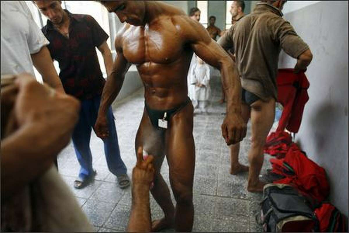 An Afghan bodybuilder gets sprayed between his legs to bring more shine to his skin backstage before competiting at a regional bodybuilding competition August 6, 2007 in Kabul, Afghanistan. Bodybuilding is a very popular sport in Afghanistan in a country where men like the image of being physically strong. It's affordable for most Afghans and its popularity is growing in many provinces. Photos of Arnold Schwarzenegger are still hanging in many local gyms as their iconic image of a muscle bound male. Photo by Paula Bronstein/Getty Images