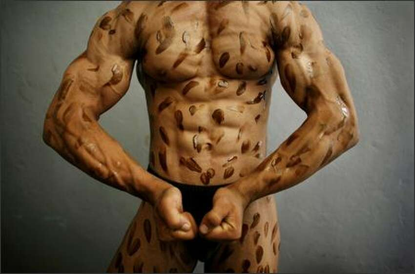 Moneer Mansoori shows off his body dotted with tanning cream backstage during a regional Bodybuilding competition August 6, 2007 in Kabul, Afghanistan. Bodybuilding is a very popular sport in Afghanistan in a country where men like the image of being physically strong. It's affordable for most Afghans and its popularity is growing in many provinces. Photos of Arnold Schwarzenegger are still hanging in many local gyms as their iconic image of a muscle bound male. Photo by Paula Bronstein/Getty Images