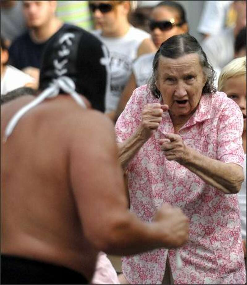 "Dorothy Brown, 90, right, prepares to fight the professional wrestler called the ""Sheek of Arabi"" Wednesday, Aug. 8, 2007, as she gets carried away by the professional wrestling action at the Champaign County Fair in Urbana, Ohio. Photo/Springfield News-Sun, Bill Lackey"