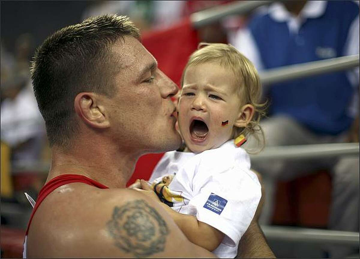 Germany's Mirko Englich kisses his crying 1-year-old daughter Lotte after he beat US' Adam Wheeler in a semi-final men's 96 kg Greco-Roman wrestling at the 2008 Olympics in Beijing, Thursday, Aug. 14, 2008. (AP Photo/David Guttenfelder)