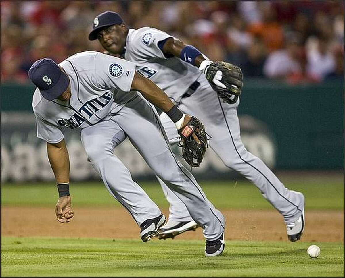 Seattle Mariners' Adrian Beltre, left, and Yuniesky Betancourt, both miss a ground ball hit by Los Angeles Angels' Mark Teixeira for a single in the third inning of a baseball game in Anaheim, Calif., Tuesday, Aug. 12, 2008. (AP Photo/Mark Avery)