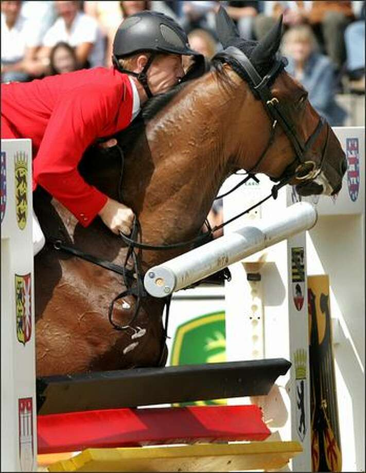 "German rider Marcus Ehning and his horse ""Nolte's Kuechengirld"" fail to clear an obstacle during the second round at the FEI Horse Jumping European Championships in Mannheim, southern Germany, Thursday, Aug. 16, 2007. AP Photo/Michael Probst"