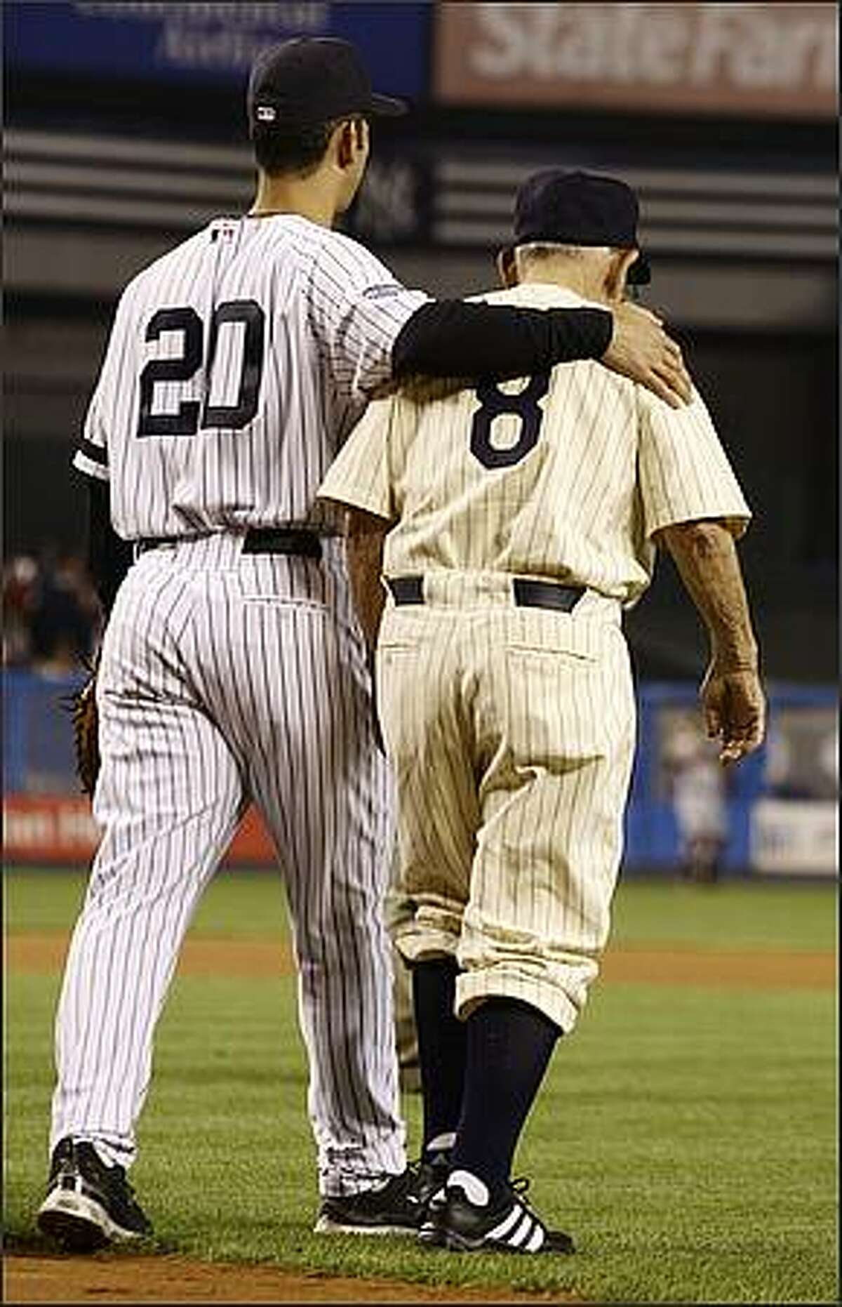 New York Yankees catcher Jorge Posada, left, walks off the field with former Yankees catcher Yogi Berra after ceremonies at Yankee Stadium in New York on Sunday, Sept. 21, 2008. The Yankees went on to face the Baltimore Orioles in what will likely be the last baseball game played at the stadium. (AP Photo/Kathy Willens)