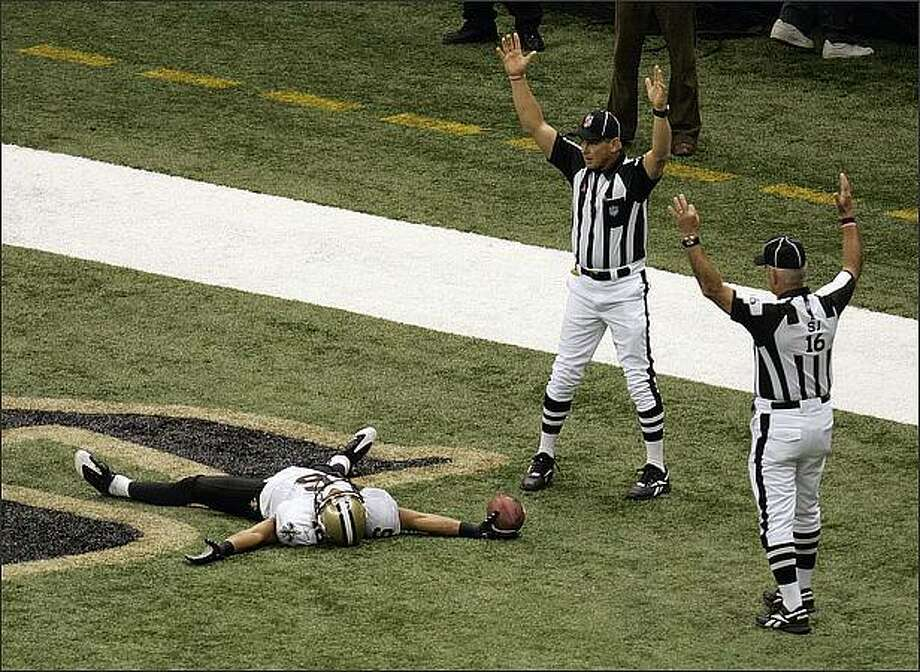 "New Orleans Saint wide receiver Lance Moore, left, and officials react to Moore's touchdown catch against the San Francisco 49ers in the first half of their NFL football game in New Orleans, Sunday, Sept. 28, 2008. NFL officials, side judge Dave Wyant (16), right, and back Judge Steve Freeman both signal ""touchdown"" as Moore stretches out on the turf. (AP Photo/Bill Haber)"