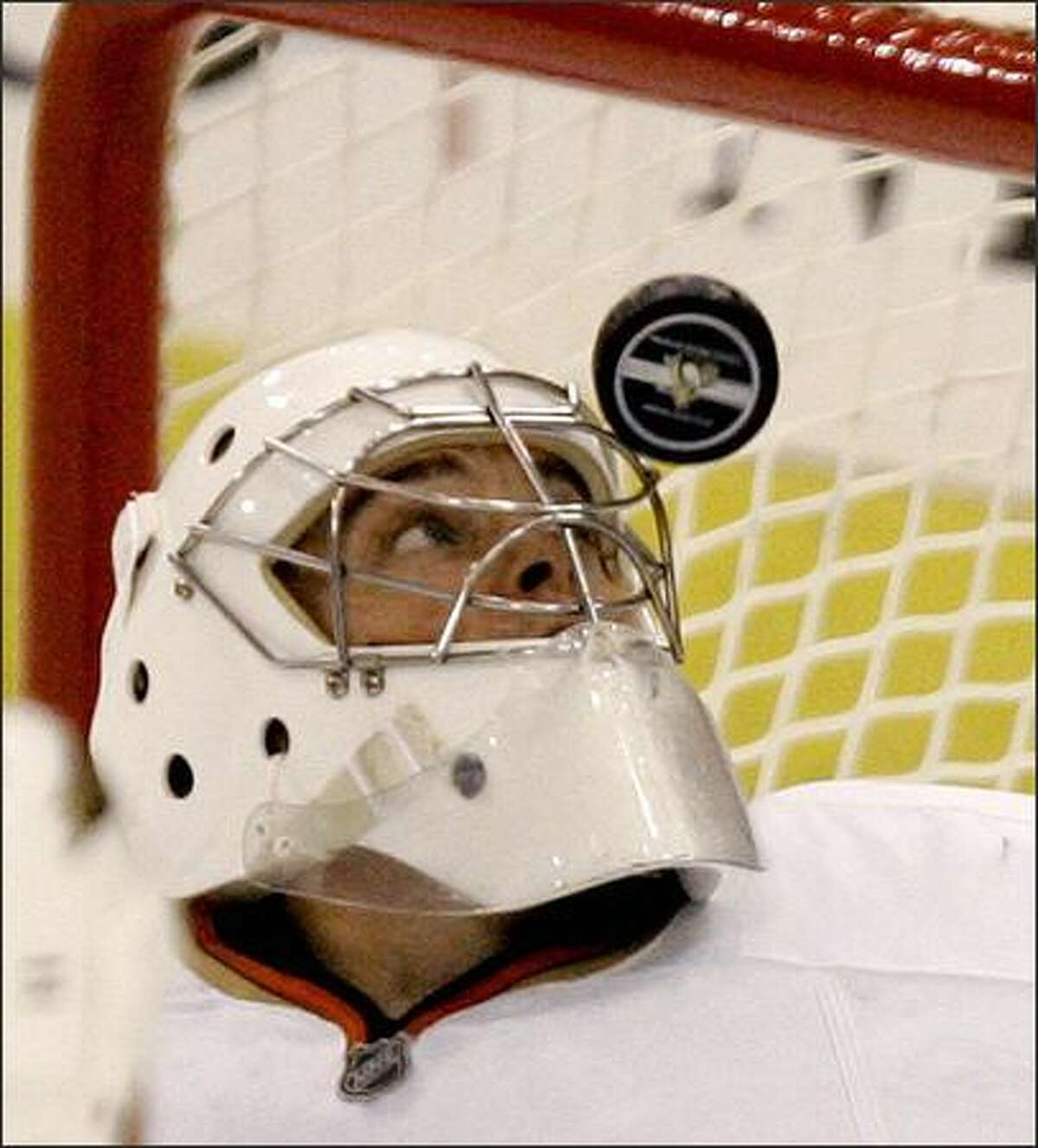 The puck bounces off the mask of Anaheim Ducks' goalie Jonas Hilleras he plays against the Pittsburgh Penguins in the first period of the hockey game in Pittsburgh,Saturday, Oct. 6, 2007. (AP Photo/Keith Srakocic)
