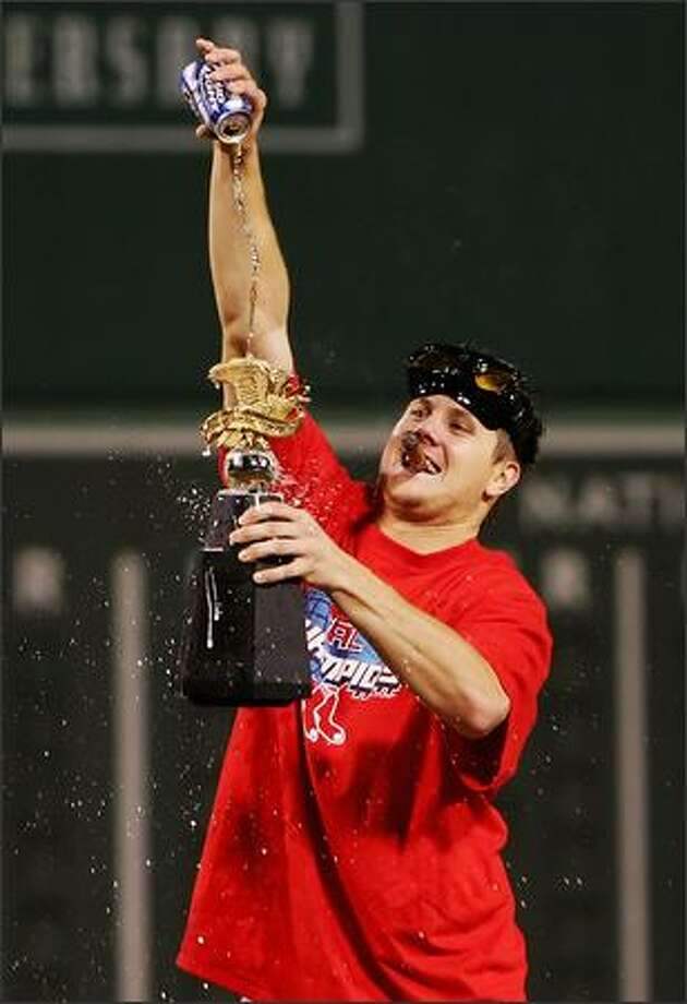 Jonathan Papelbon #58 of the Boston Red Sox pours a beer over the William Harridge Trophy after defeating the Cleveland Indians by the score of 11-2 to win the American League Championship Series at Fenway Park. (Photo by Al Bello/Getty Images)