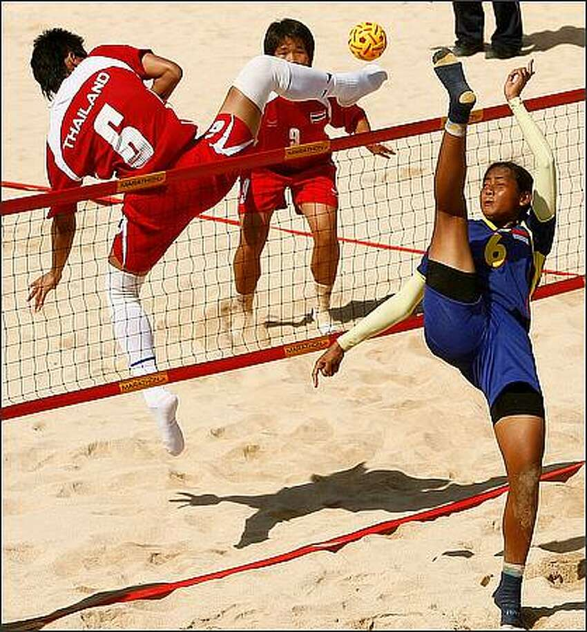 Tidawan Daosakul of Thailand and Lena of Indonesia contest at the net for a ball during the Women's Beach Sepaktakraw gold medal match between Thailand and Indonesia on day four of the 2008 Asian Beach Games at Sanur Beach in Bali, Indonesia. (Photo by Quinn Rooney/Getty Images)