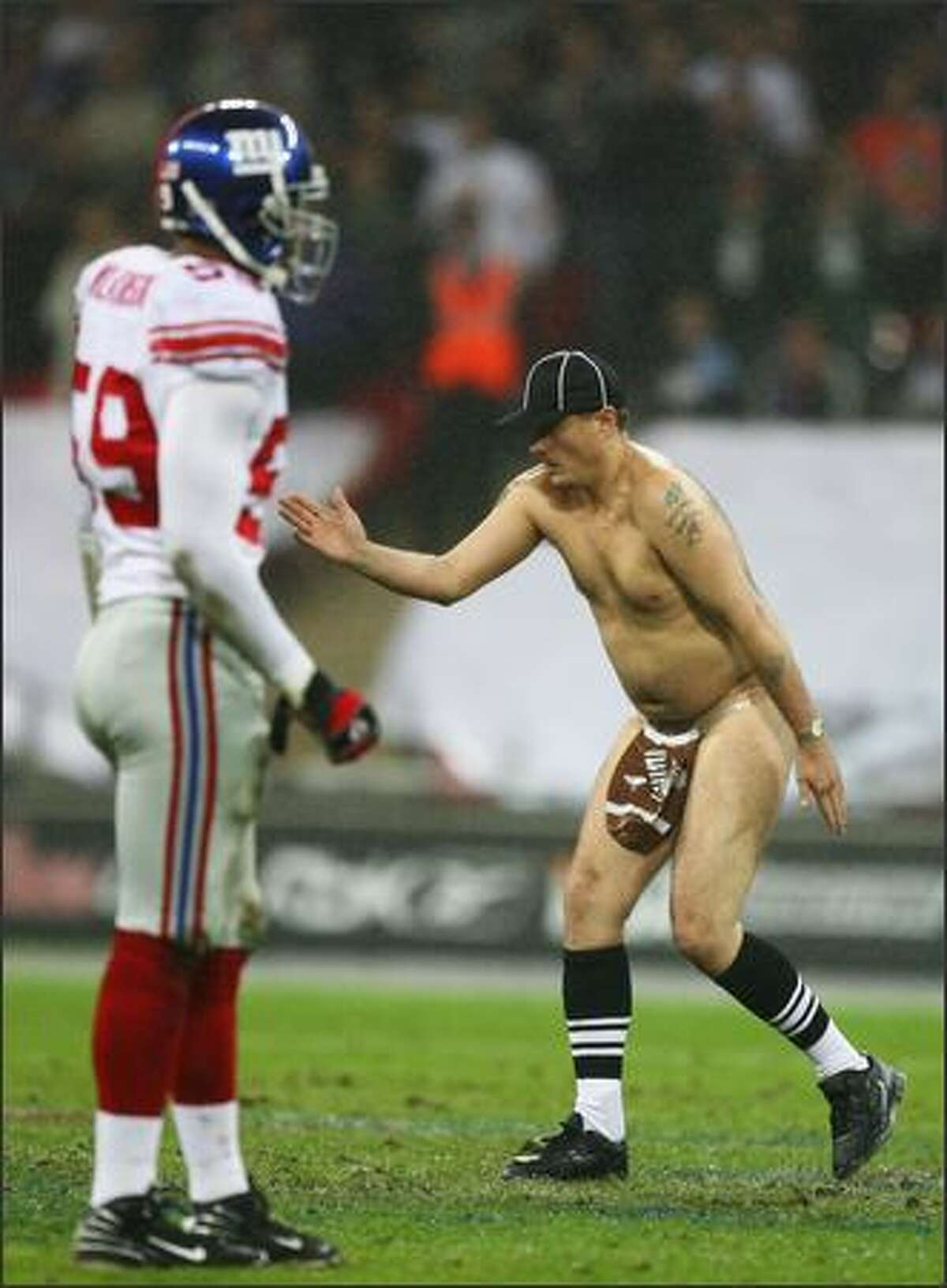 'Serial streaker' Mark Roberts dances on the field of play during the NFL Bridgestone International Series match between New York Giants and Miami Dolphins at Wembley Stadium in London, England. This is the first ever regular season NFL match to be played outside of the United States. (Photo by Al Bello/Getty Images)