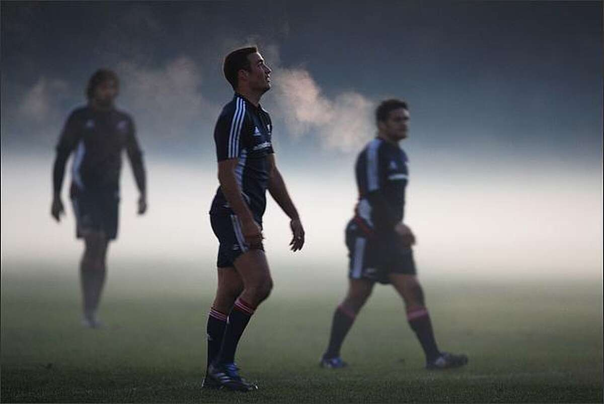 (L-R) Ross Filipo, Richard Kaui and Piri Weepu of the New Zealand All Blacks emerg from the fog during an All Blacks training session held at Perffermill fields in Edinburgh, Scotland. (Photo by Ross Land/Getty Images)