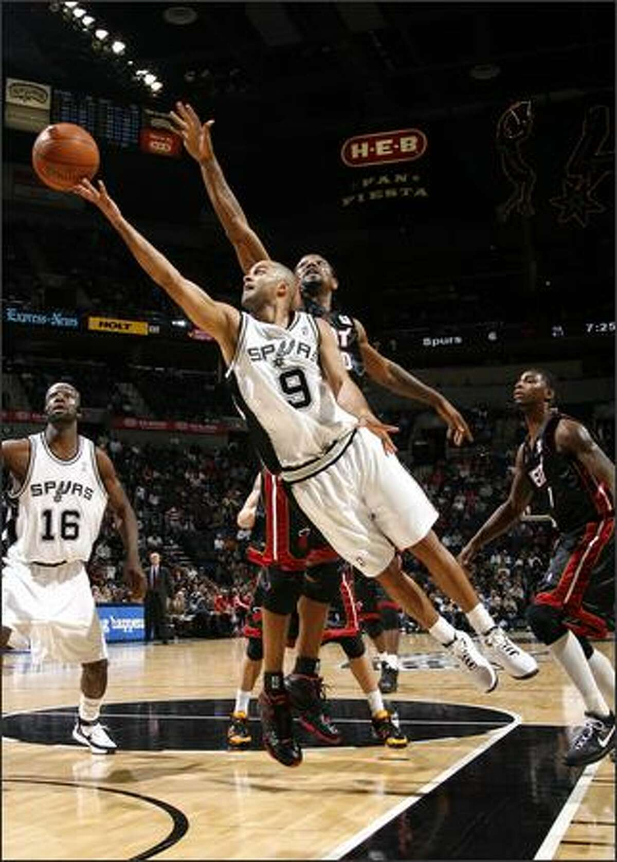 Tony Parker #9 of the San Antonio Spurs drives to the basket for a layup past Udonis Haslem #40 of the Miami Heat during a game at the AT&T Center in San Antonio, Texas. (Photo by Joe Murphy/NBAE via Getty Images)
