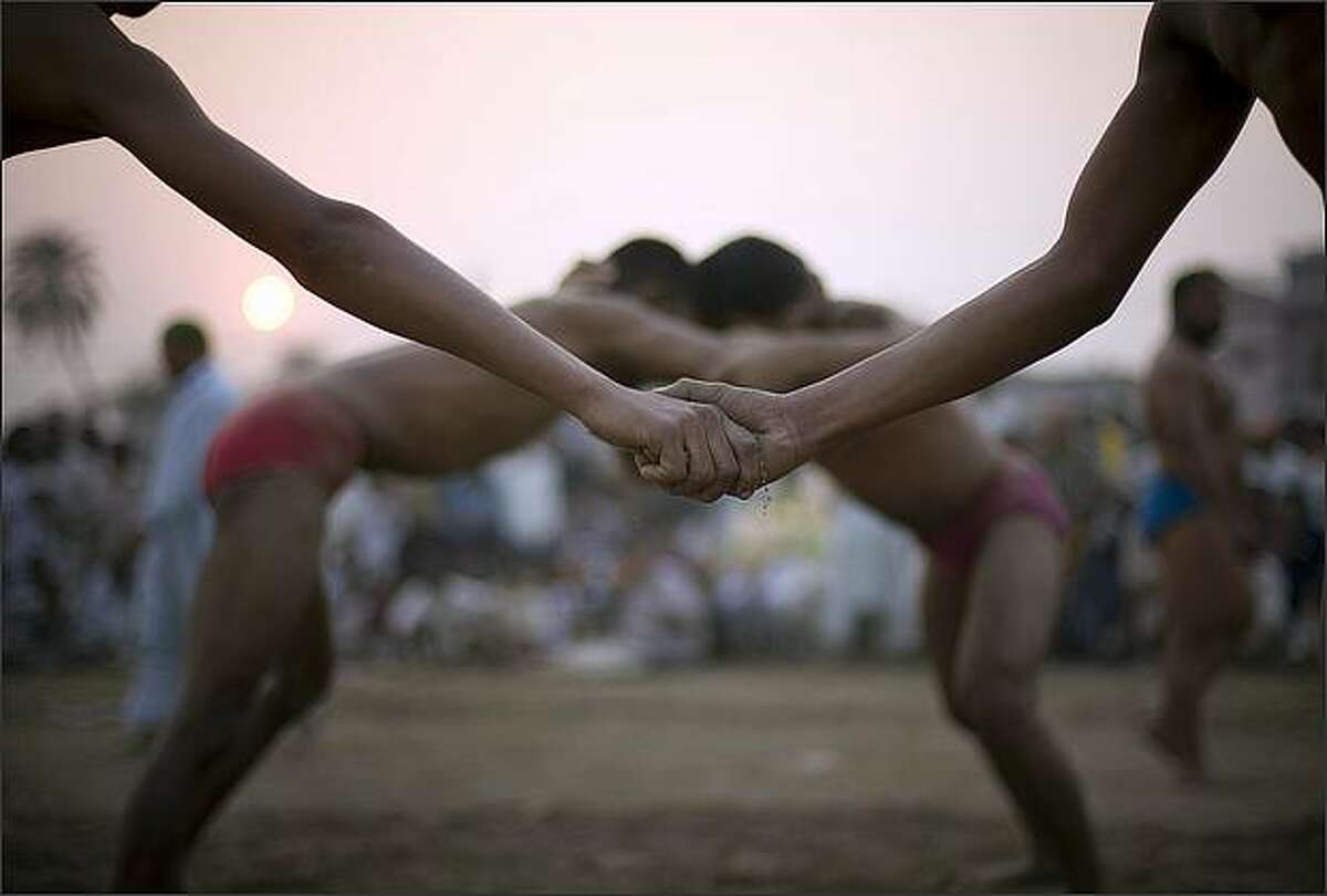 Pakistani wrestlers join their hands sharing the soil as part of a ritual before fighting during a local competition in Lahore, Pakistan. Kushti, an Indo-Pakistani form of wrestling, is several thousand years old and is a national sport in Pakistan. (AP Photo/Emilio Morenatti)