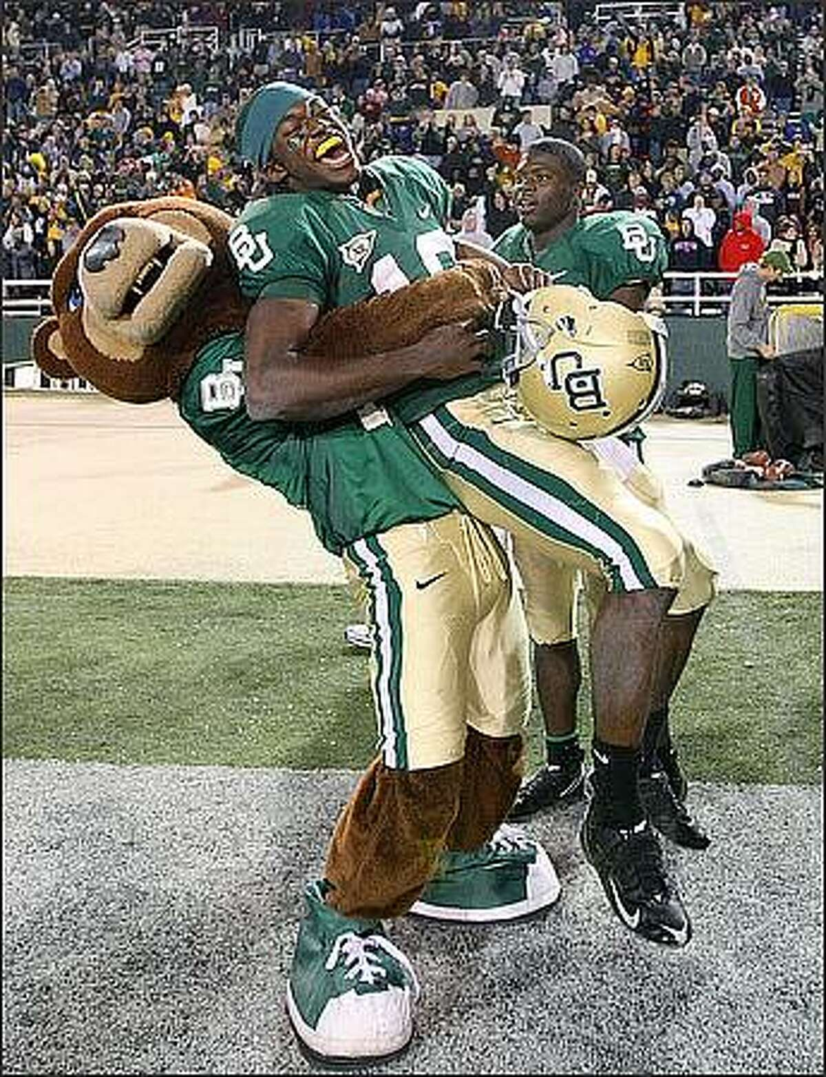 Baylor quarterback Robert Griffin is hugged by Bruiser, the University's mascot, after defeating Texas A&M 41-21 in an NCAA college football game in Waco, Texas. (AP Photo/Waco Tribune Herald, Jerry Larson)