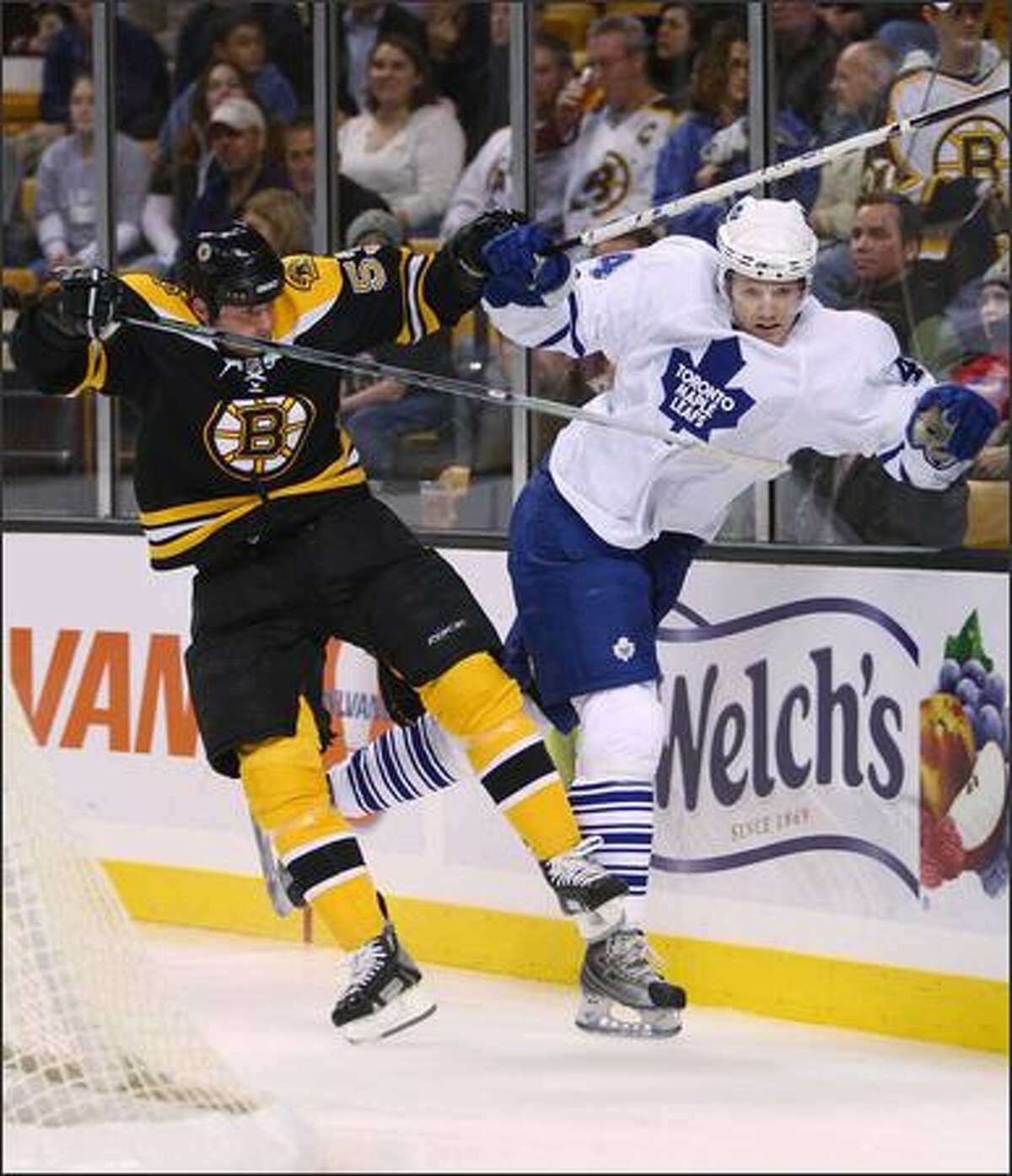 Jeremy Reich #53 of the Boston Bruins and Staffan Kronwall #44 of the Toronto Maple Leafs collide at the TD Banknorth Garden in Boston, Massachusetts. (Photo by Elsa/Getty Images)