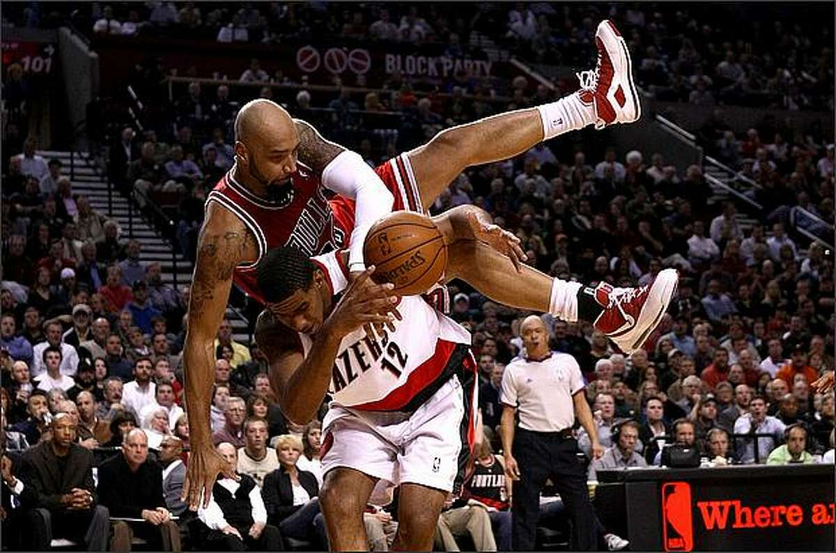 Drew Gooden #90 of the Chicago Bulls falls over the top of LaMarcus Aldridge #12 of the Portland Trail Blazers at the Rose Garden in Portland, Oregon. (Photo by Jonathan Ferrey/Getty Images)