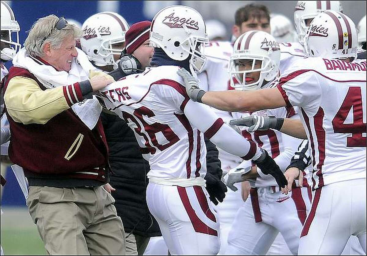 New Mexico State head coach Hal Mumme, left, pulls Mark Waters out of a fight with a Utah State player during an NCAA college football game in Logan, Utah. (AP Photo/The Herald Journal, Eli Lucero)