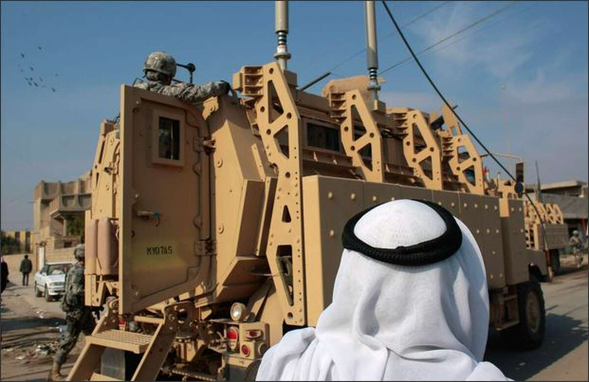 An Iraqi man stands by an American troop transport vehicle January 19, 2009 in Musayyib, in the Babil Province, Iraq. Musayyib was once an explosively dangerous zone for American troops; now a fragile peace is at hand, as the area's restive Shia and Sunni groups formed U.S.-sanctioned militias to keep order. American troops are stepping up patrols in advance of important Iraqi elections on January 31.