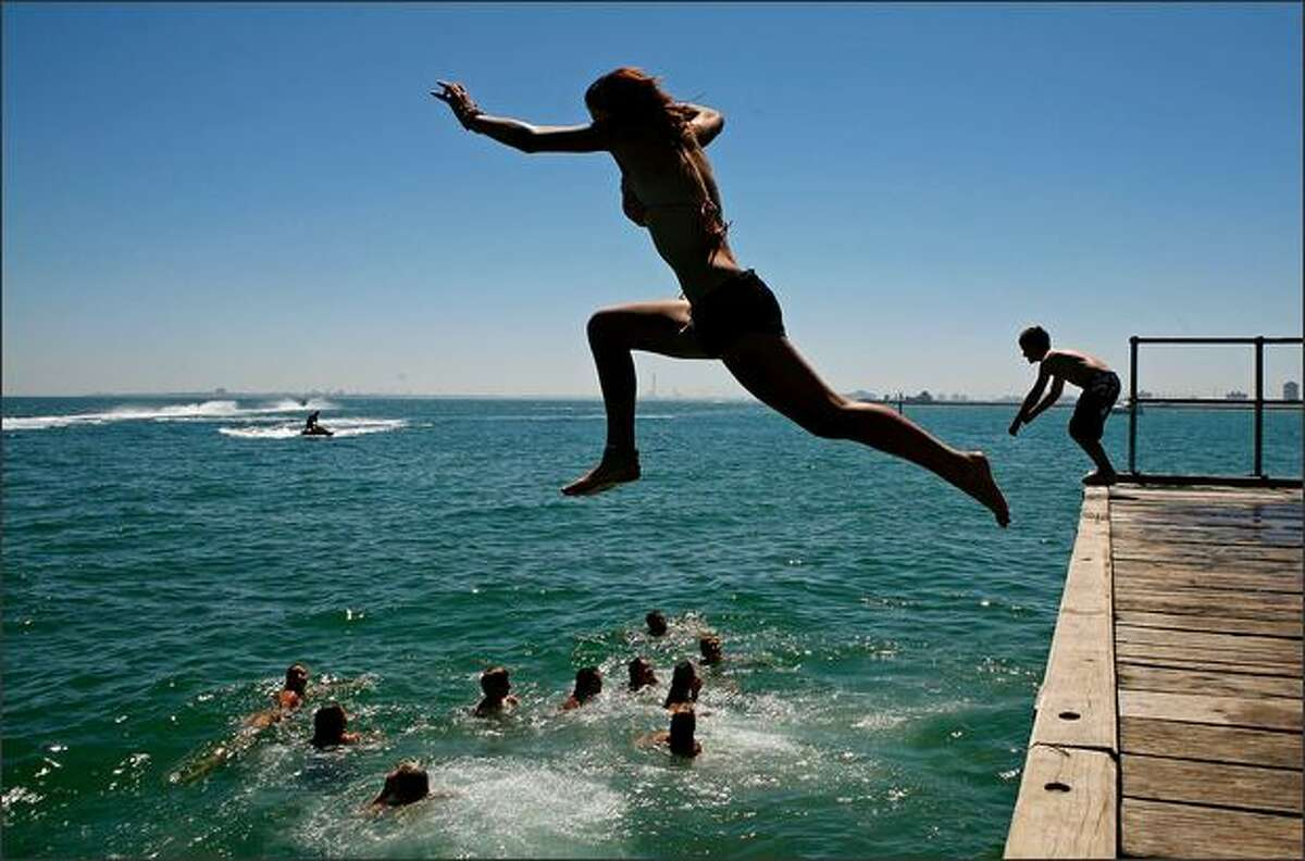 People jump of the pier at St Kilda beach as a heatwave hits Melbourne on Tuesday in Melbourne, Australia. The temperature today is estimated to hit 38 degrees celsius or around 100 degrees fahrenheit, with today being the coolest day forecast until next week. Melbourne hasn't had four consecutive days above 40 degrees celsius or 104 degrees fahrenheit since 1908.