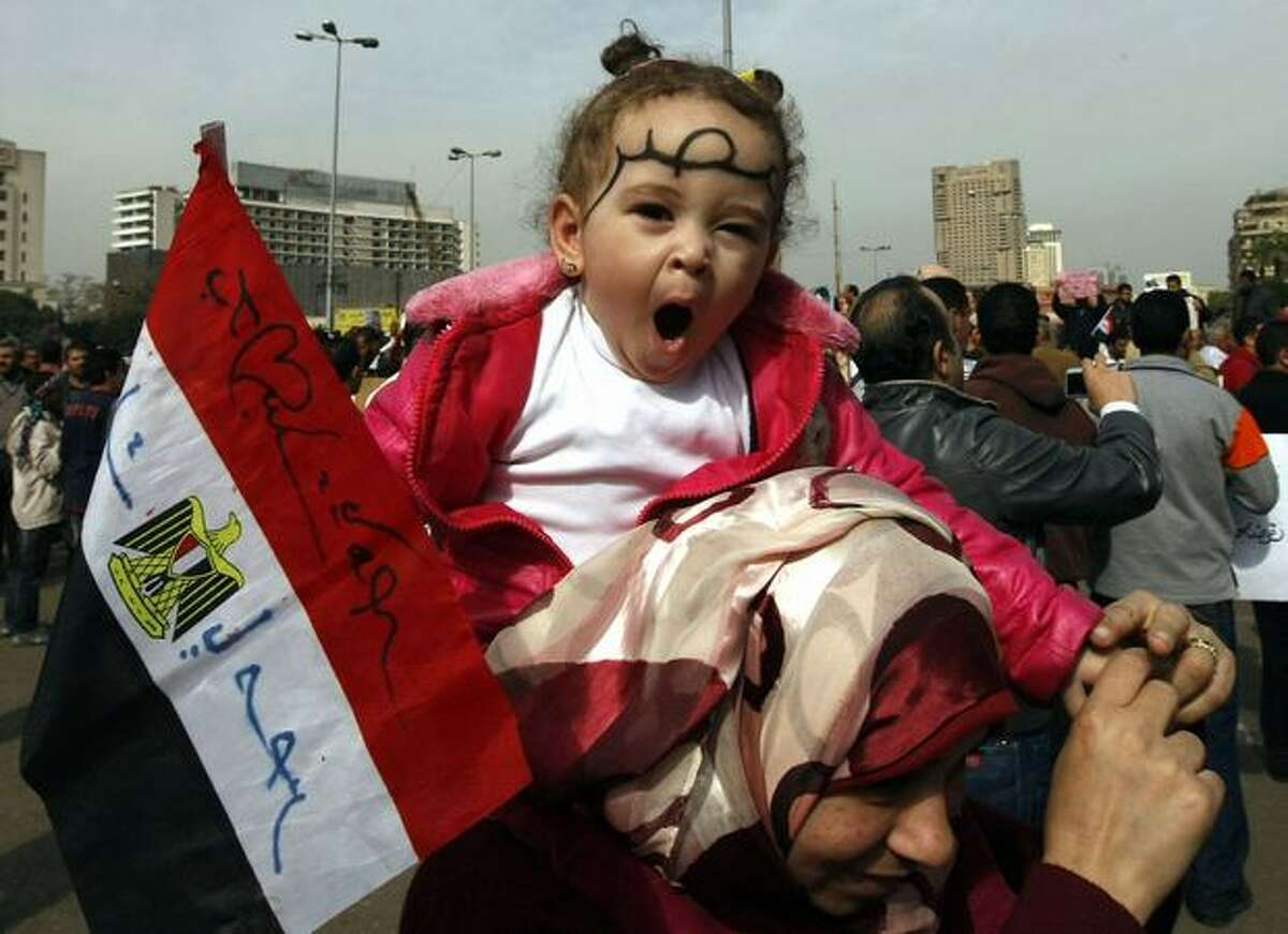 A mother on Tuesday carries her daughter on her shoulders with the word