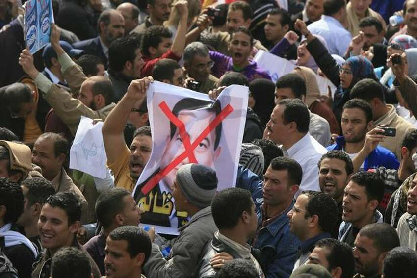 A poster of Hosni Mubarak with his face crossed out is held up Tuesday as Egyptians gather in Cairo's Tahrir Square heeding a call by the opposition for a