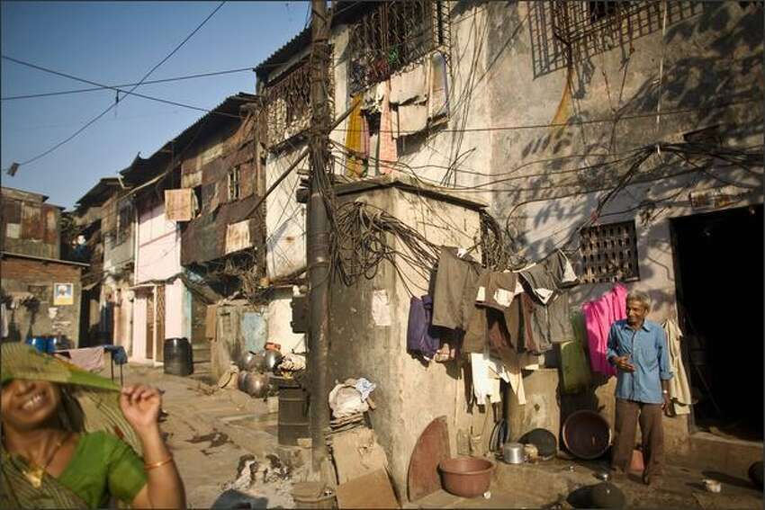 Dwellers move through the Dharavi slum on Monday in Mumbai, India. The redevelopment of asia's largest slum, the Dharavi, spanning over 535-acres and situated in the heart of the world's third largest city and India's financial capital, has been stalled by the economic financial crisis, bad press and local protests.