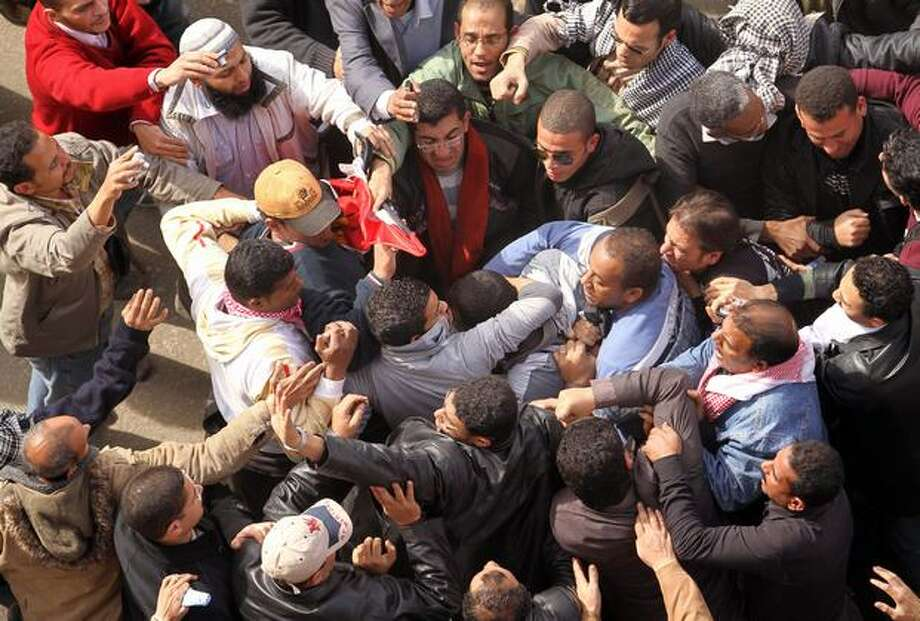 Egyptian protesters opposed to President Hosni Mubarak detain a government supporter during protests on Thursday near Cairo's central Tahrir Square where crowds have gathered for days to call for the ouster of the embattled president. Photo: Getty Images / Getty Images