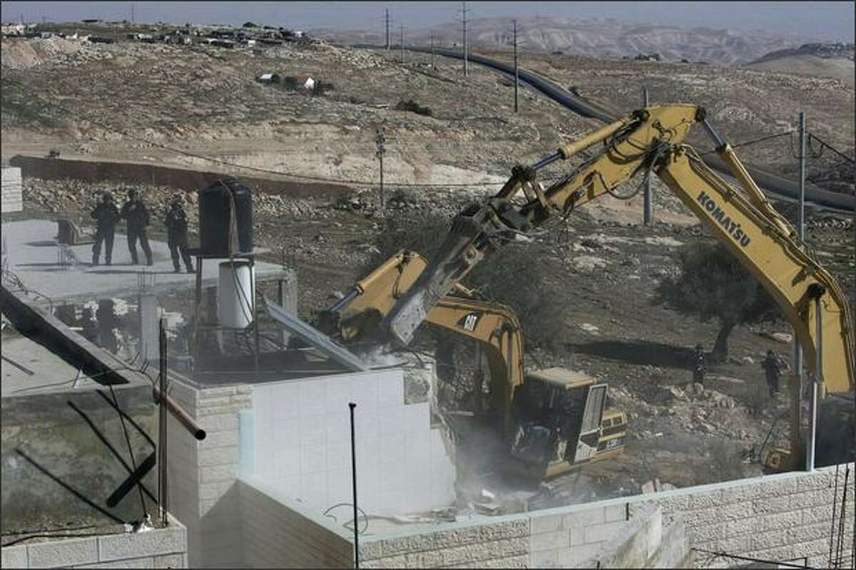 Israeli forces keep watch while a bulldozer demolishes a Palestinian house that was built without municipality permission in the Jerusalem Arab neighborhood of Isawiyya on Wednesday. US Middle East envoy George Mitchell will meet Palestinian president Mahmud Abbas on February 26 on his second visit to the region in a month. This second visit since his appointment in January confirms the real interest the administration of President Barack Obama has in a settlement of the Israeli-Palestinian conflict.