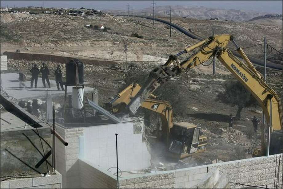 Israeli forces keep watch while a bulldozer demolishes a Palestinian house that was built without municipality permission in the Jerusalem Arab neighborhood of Isawiyya on Wednesday. US Middle East envoy George Mitchell will meet Palestinian president Mahmud Abbas on February 26 on his second visit to the region in a month. This second visit since his appointment in January confirms the real interest the administration of President Barack Obama has in a settlement of the Israeli-Palestinian conflict. Photo: Getty Images / Getty Images