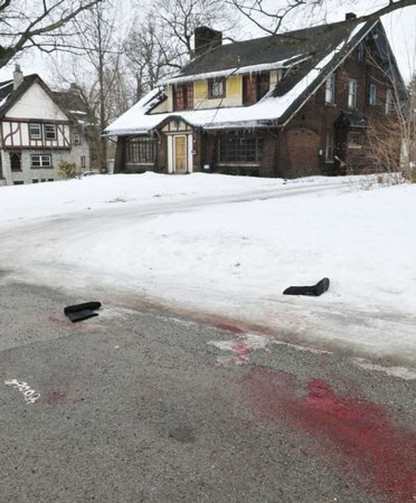 What appears to be blood stains the street near the scene of an early morning shooting at a house just north of the Youngstown State University campus that left student Jamail E. Johnson, 25 of Youngstown, dead and 11 injured, In Youngstown, Ohio on Sunday. (AP Photo/Mark Stahl)