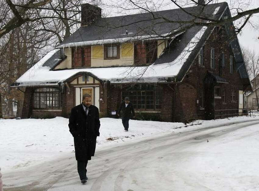 Phil Walls, brother of one of the shooting victims, leaves a house in Youngstown, Ohio Monday where one college student was killed and 11 injured early Sunday. A day after an admired college student was shot dead and 11 people were injured, the governor, college officials and friends were seeking an explanation for the violence. (AP Photo/Tony Dejak)