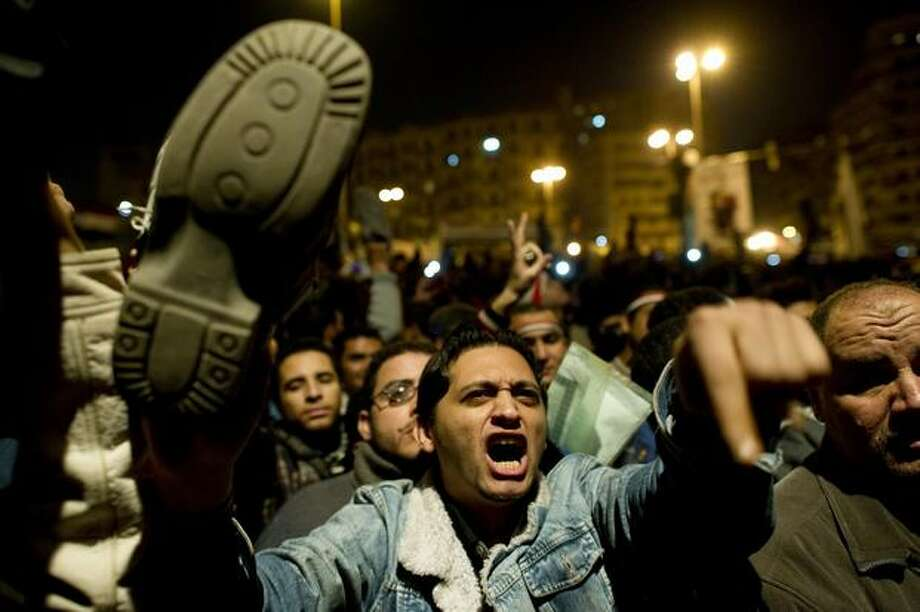 An Egyptian anti-government demonstrator waves a shoe Thursday in Cairo's Tahrir Square as he shows his anger during a speech by Egyptian President Hosni Mubarak, who failed to announce his immediate resignation. Embattled Mubarak delegated power to his deputy and former intelligence chief Omar Suleiman and proposed constitutional reforms but said the transition to end his 30-year-reign would last until September. Photo: Getty Images / Getty Images