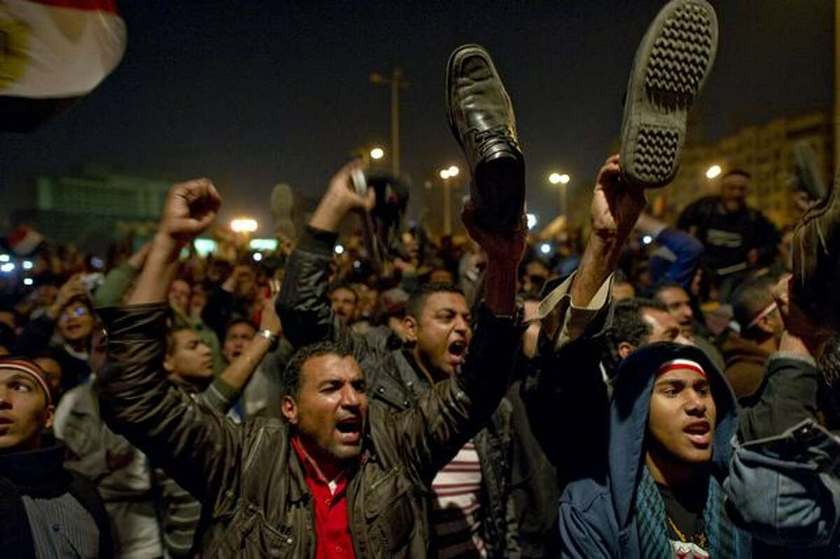 Egyptian anti-government demonstrators wave their shoes as they show their anger during a speech by Egyptian President Hosni Mubarak, who failed to announce his immediate resignation, as tens of thousands gathered in Cairo's Tahrir Square on Thursday.
