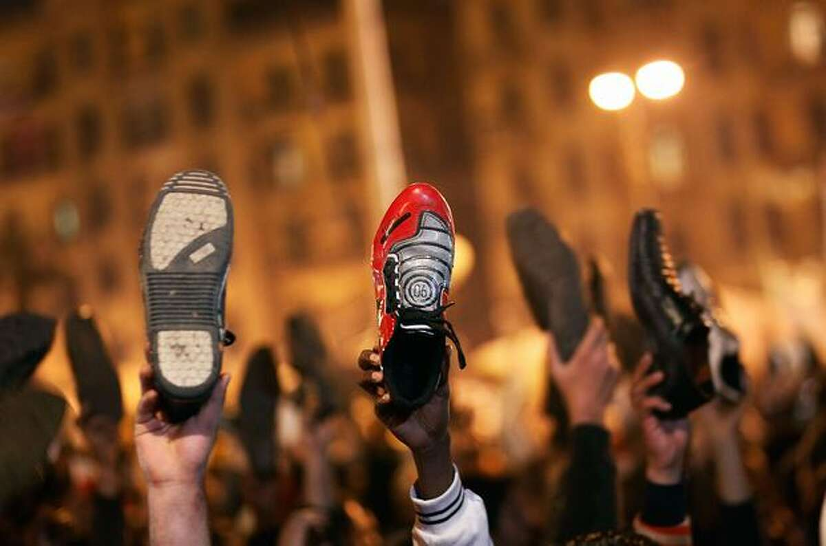 Anti-government protesters raise their shoes after a speech by Egyptian President Hosni Mubarek on Thursday in Cairo, Egypt. President Hosni Mubarak made a statement saying that he had given some powers to his vice president but would not resign or leave the country, leaving a crowd of anti-government protesters disappointed and furious after early reports he might step down.