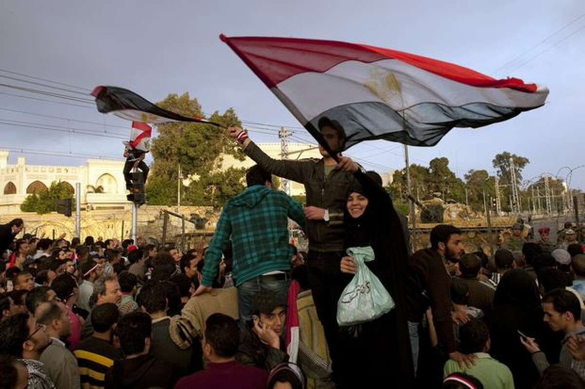 Egyptian anti-goverment protesters gather outside the Presidential Palace in Cairo on Friday. Cairo's streets exploded in joy when President Hosni Mubarak stepped down after three-decades of autocratic rule and handed power to a junta of senior military commanders.