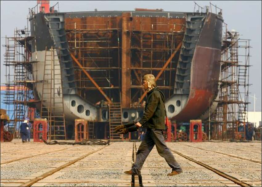 A worker walks the giant hulk of a ship being built at a Chongqing Changhang Dongfeng Vessel Industry Company dock on February 12, 2009 in Chongqing, China. China's State Council has sanctioned a stimulus package for the ship building industry at an executive meeting chaired by Chinese PM Wen Jiabao. The meeting confirmed an increase in credit support for ship buyers and maintain the existing financial support policies for oceangoing vessels until 2012, state media said.