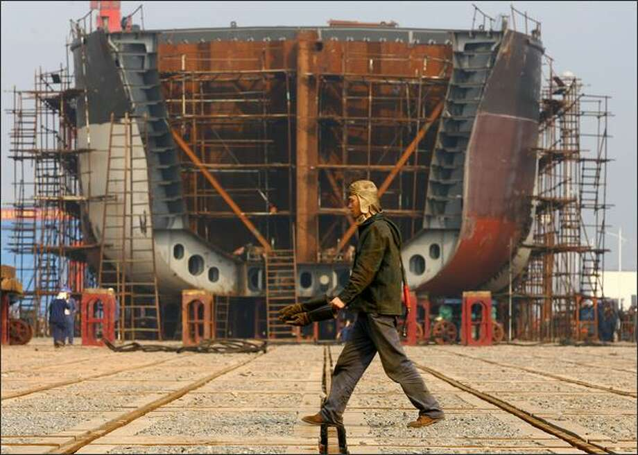 A worker walks the giant hulk of a ship being built at a Chongqing Changhang Dongfeng Vessel Industry Company dock on February 12, 2009 in Chongqing, China. China's State Council has sanctioned a stimulus package for the ship building industry at an executive meeting chaired by Chinese PM Wen Jiabao. The meeting confirmed an increase in credit support for ship buyers and maintain the existing financial support policies for oceangoing vessels until 2012, state media said. Photo: Getty Images / Getty Images