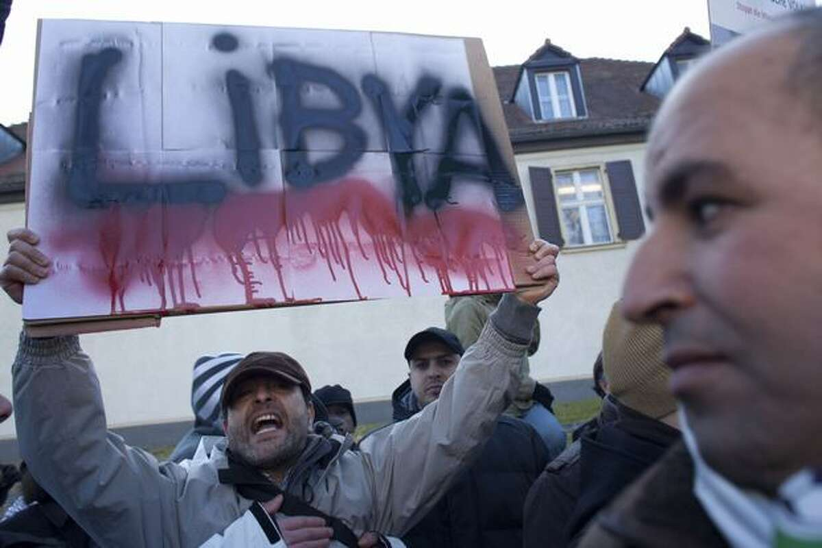 Demonstrators hold posters as they call for the ouster of Libyan leader Moammar Gadhafi near the Libyan embassy in Berlin on Monday. (AP Photo/Markus Schreiber)