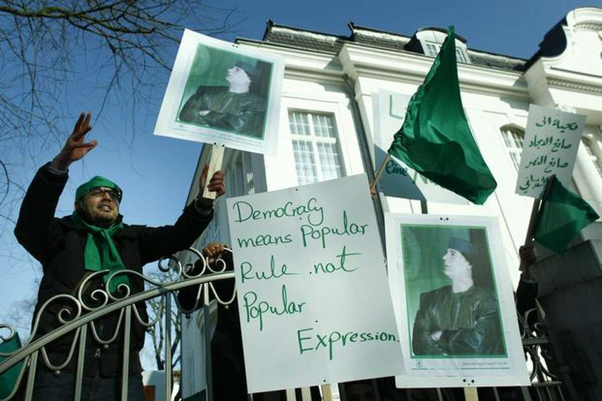 Supporters of Libyan leader Moammar Gadhafi with posters stand behind the fence of the Libyan embassy and shout slogans against protesters outside the embassy in Berlin on Monday. (AP Photo/Markus Schreiber)