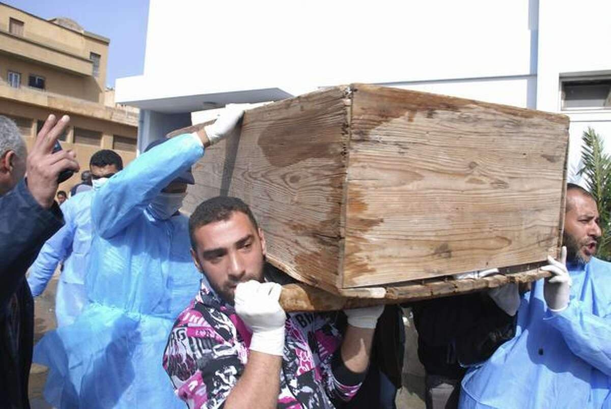 Men carry a coffin at Al-Jalaa hospital in Benghazi, Libya on Monday. Libyan protesters celebrated in the streets of Benghazi on Monday, claiming control of the country's second largest city after bloody fighting, and anti-government unrest spread to the capital with clashes in Tripoli's main square for the first time. (AP Photo/Alaguri)