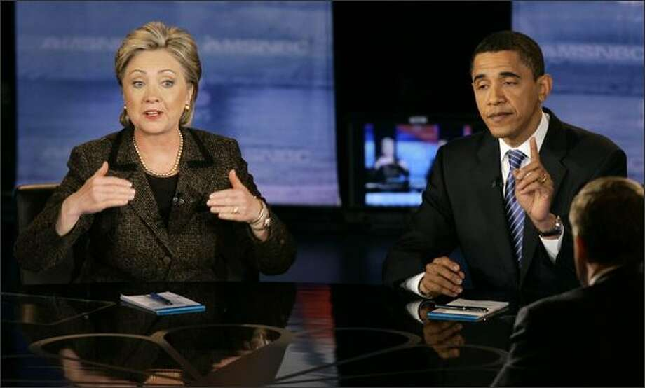 Democratic presidential hopefuls Sen. Hillary Rodham Clinton, D-N.Y., left, and Sen. Barack Obama, D-Ill., respond to a question during a Democratic presidential debate Tuesday, in Cleveland. (AP Photo/Kiichiro Sato) - The story