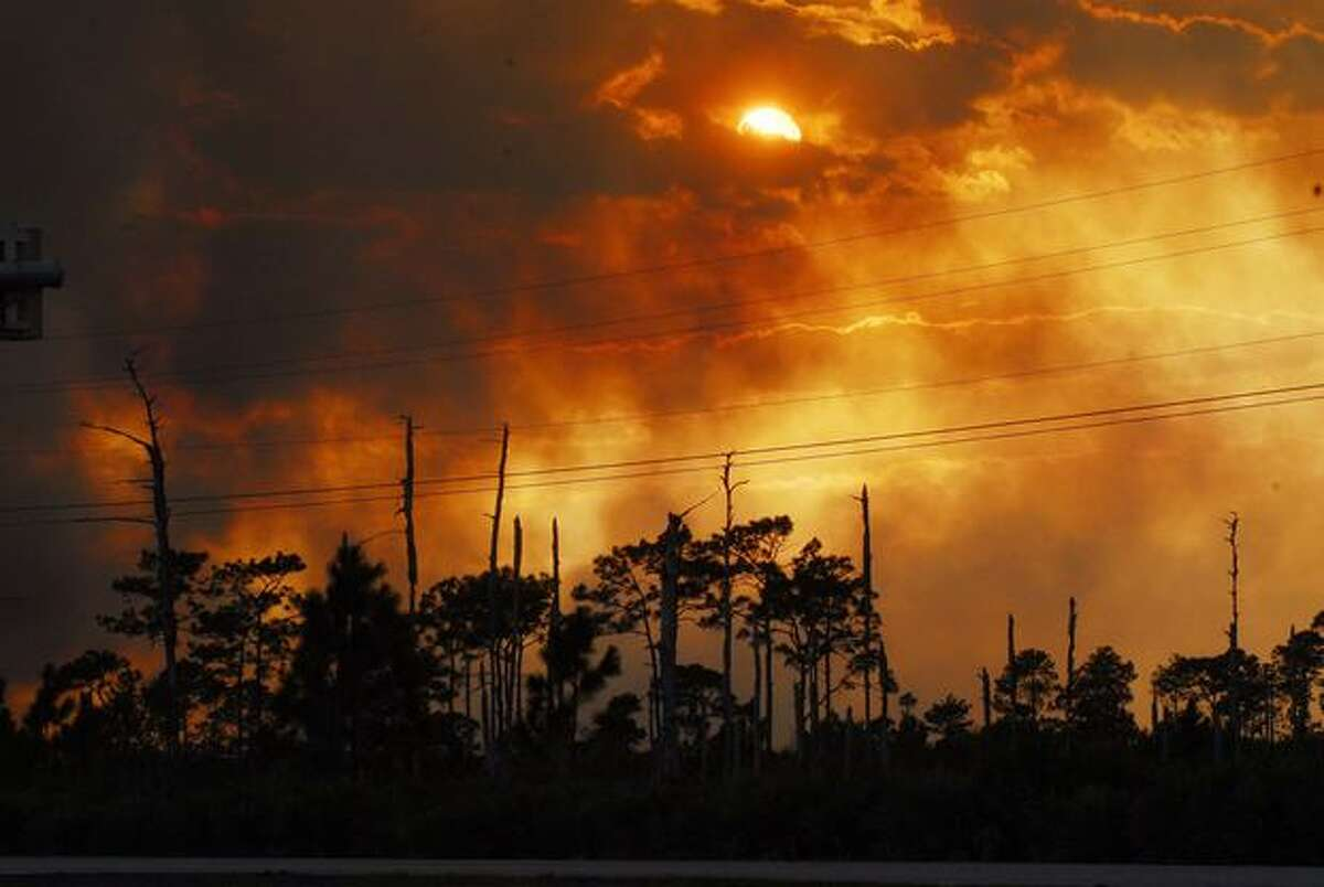 In this Monday photo, flames from a brush fire light up the sky as more than 10,000 acres burn west of Interstate 95 at the Volusia and Brevard County line in the Scottsmoor, Fla., area. (AP Photo/Florida Today, Craig Rubadoux)
