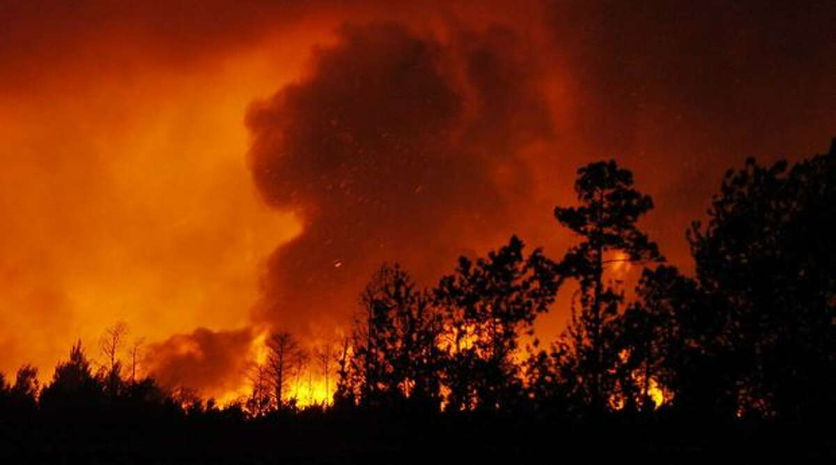 In this Monday, photo, flames from a brush fire light up the sky as more than 10,000 acres burn west of Interstate 95 at the Volusia and Brevard County line in the Scottsmoor, Fla., area. (AP Photo/Florida Today, Craig Rubadoux)