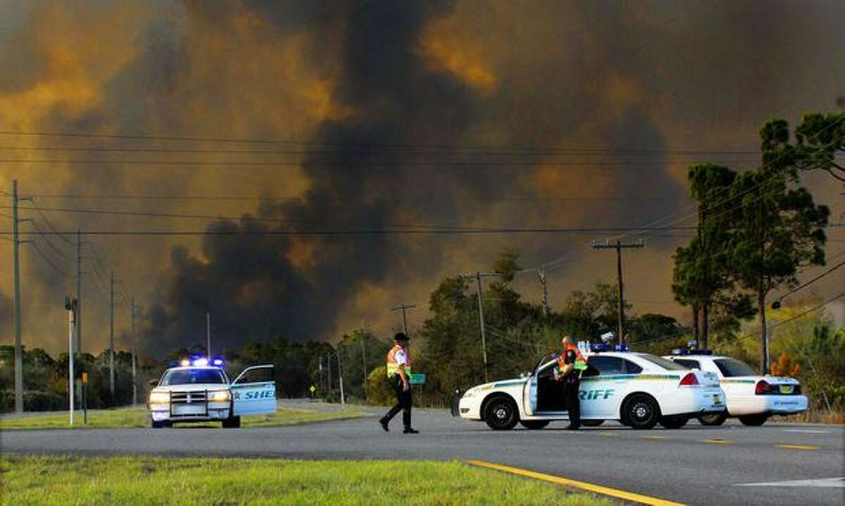 In this Monday, photo, Brevard County sheriff's deputies close U.S. Route 1, in Scottsmoor, Fla., due to a 10,000-acre brush fire burning near the Volusia and Brevard County line. The Florida Highway Patrol has reopened a roughly 30-mile stretch of Interstate 95 on the state's central Atlantic coast that was closed because of the fast-moving wildfire. Rain was in the forecast Tuesday as officials opened all lanes of Interstate 95 in Brevard County. They also reopened U.S. Route 1. The Highway Patrol still urges motorists to use caution in the area. (AP Photo/Florida Today, Craig Rubadoux)