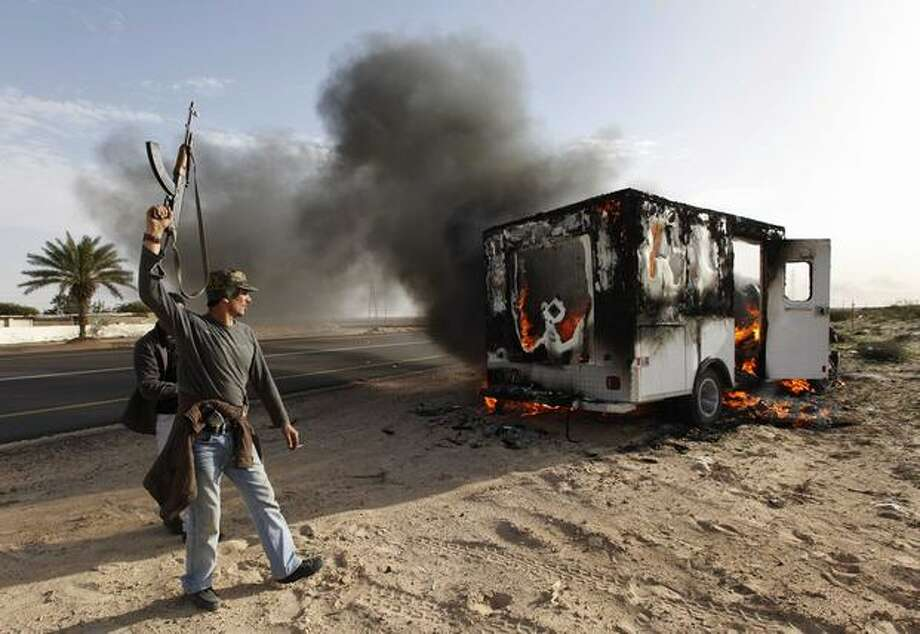 A Libyan rebel celebrates next to a burning vehicle in the town of Brega, east of Libya, on Wednesday. Regime opponents battled forces loyal to Libyan leader Moammar Gadhafi who tried Wednesday to retake a key oil installation in a counteroffensive Wednesday against the rebel-held eastern half of the country. At one point in the flip-flopping battle, anti-Gadhafi fighters cornered the attackers in a nearby seaside university campus in fierce fighting that killed at least five. (AP Photo/Hussein Malla) Photo: Associated Press / Associated Press