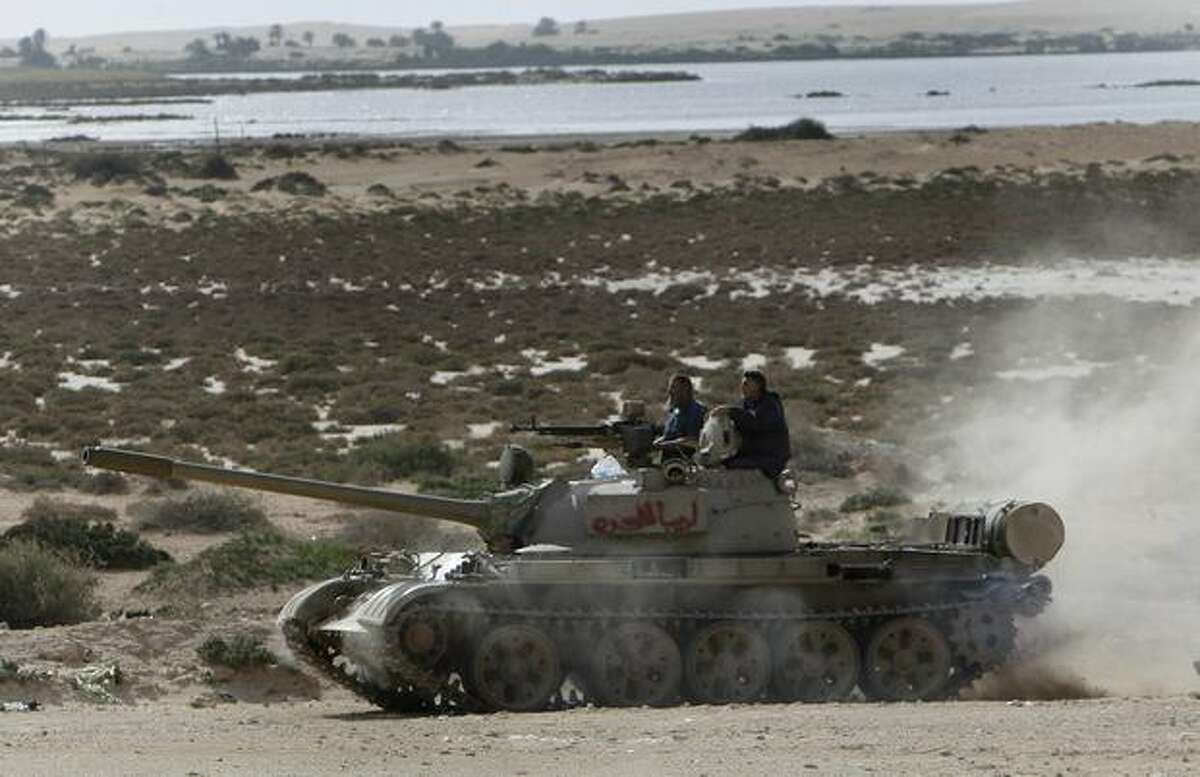 Libyan rebels stand on their tank driving forward to battle against pro-Moaamar Gadhafi fighters, in the town of Brega, east of Libya, on Wednesday. Regime opponents battled forces loyal to Libyan leader Moammar Gadhafi who tried Wednesday to retake a key oil installation in a counteroffensive Wednesday against the rebel-held eastern half of the country. At one point in the flip-flopping battle, anti-Gadhafi fighters cornered the attackers in a nearby seaside university campus in fierce fighting that killed at least five. (AP Photo/Hussein Malla)