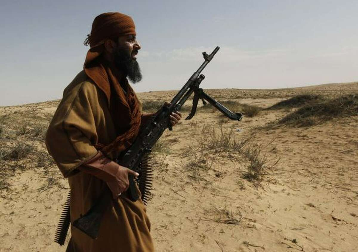 A Libyan rebel moves holds his automatic rifle as he walks forward during a battle against pro-Moaamar Gadhafi fighters, in the town of Brega, east of Libya, on Wednesday. Regime opponents battled forces loyal to Libyan leader Moammar Gadhafi who tried Wednesday to retake a key oil installation in a counteroffensive Wednesday against the rebel-held eastern half of the country. At one point in the flip-flopping battle, anti-Gadhafi fighters cornered the attackers in a nearby seaside university campus in fierce fighting that killed at least five. (AP Photo/Hussein Malla)