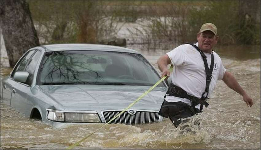 Rickey Joe Smith, owner of Eddie's Towing, pulls a car from moving water left by storms from the night before, as another car is swept off on Cedar Creek Church Rd in Falkville, Ala., Tuesday. (Jonathan Palmer/The Decatur Daily)