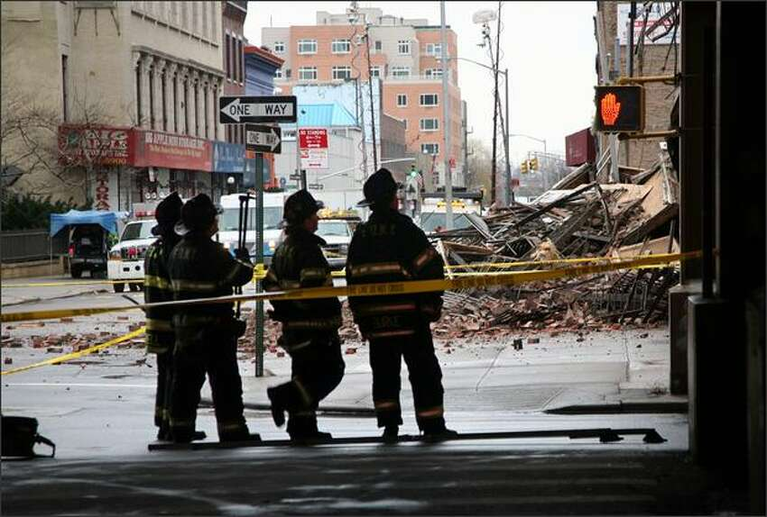 Firefighters gather around debris from a building collapse on 124 St. and Park Ave. in Harlem, New York which forced Metro North to suspend service Tuesday. (AP Photo/David Karp)
