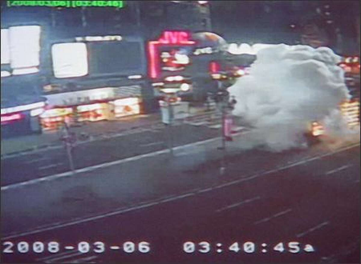 This photo released by the New York Police Dept. from a private security camera shows an explosion at the Times Square military recruiting station Thursday in New York. Police released footage from a private security camera on Thursday showing a cyclist riding up to the station where a small bomb was detonated. (AP Photo/New York Police Dept.) - Story: NYC struck again by mystery bomber
