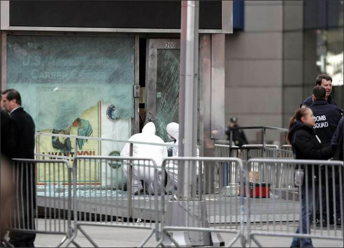 New York police officers with the bomb squad unit inspect the damage done by an explosive device to the military recruitment center Thursday, in New York's Times Square. New York City police say some kind of explosive device was set off near a military recruiting station in Times Square. Police say there were no injuries in the blast early Thursday morning. The recruiting center at 43rd Street near Broadway had a large hole in the front window. (AP Photo/David Karp) - Story: NYC struck again by mystery bomber