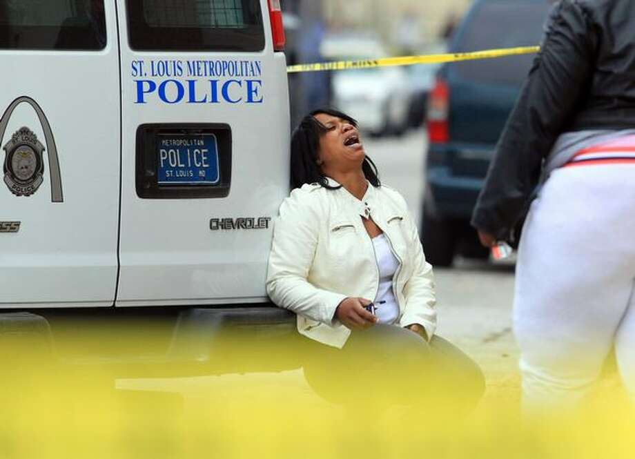 A relative of a man involved in a standoff with St. Louis police reacts after a police tactical team entered a house in the 3100 block of Osage, on Tuesday in St. Louis. The suspect was found dead. (AP Photo/St. Louis Post-Dispatch, Christian Gooden) Photo: Associated Press / Associated Press